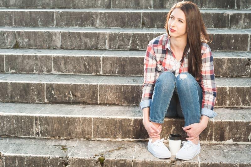 Junges attraktives weibliches Sitzen auf Treppe mit einer Kaffeetasse lizenzfreie stockfotografie