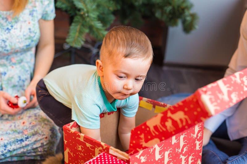 Junges Baby, das eine Geschenkbox öffnet stockbild