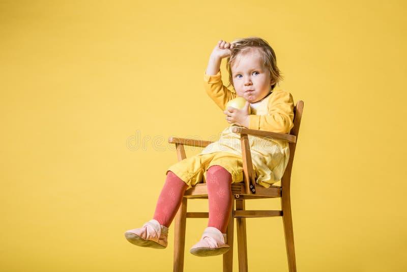 Junges Baby im gelben Kleid auf gelbem Hintergrund stockfotos