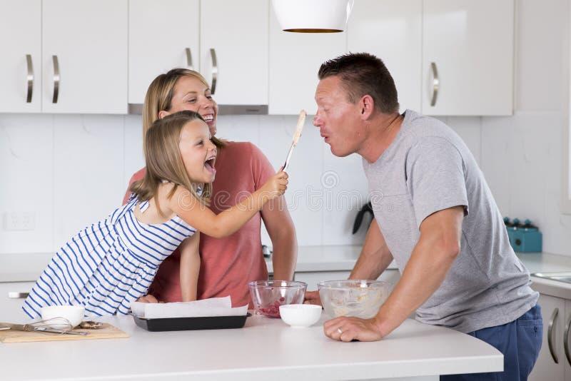 Junges Backen des glücklichen Paars zusammen mit der kleinen jungen schönen Küche der Tochter zu Hause, die den Spaß mit Sahne sp lizenzfreies stockbild