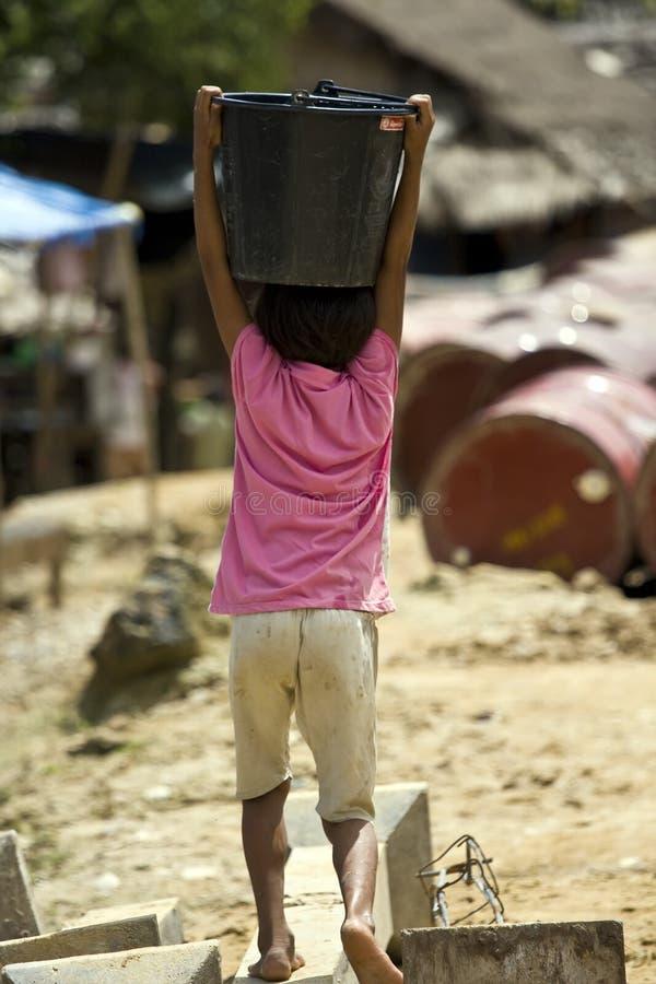 Junges birmanisches Mädchen trägt Wasser in einem Flüchtlingslager in Thailand lizenzfreie stockfotografie