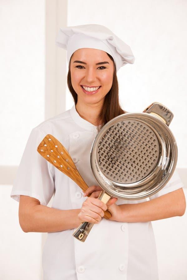 Junges blondes Chef woamn hält Küchengeschirr, während sie sich vorbereitet zu gurren lizenzfreie stockfotografie