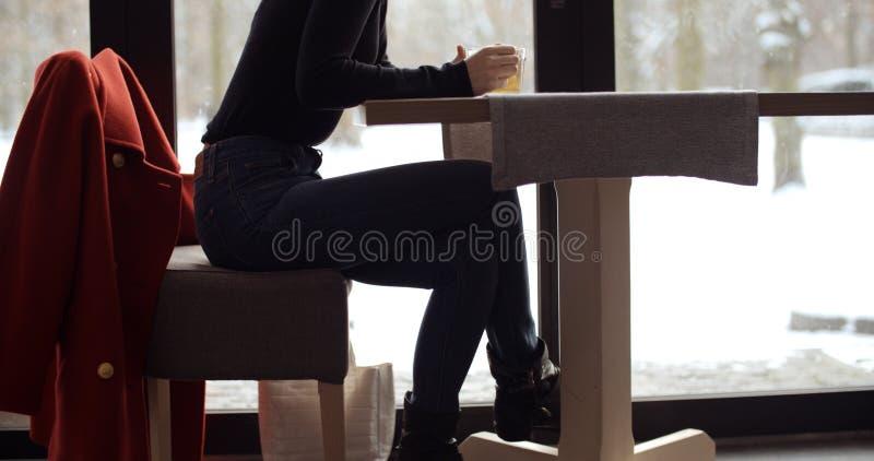 Junges blondes Mädchen, das ihren Tee im Restaurant genießt lizenzfreies stockbild