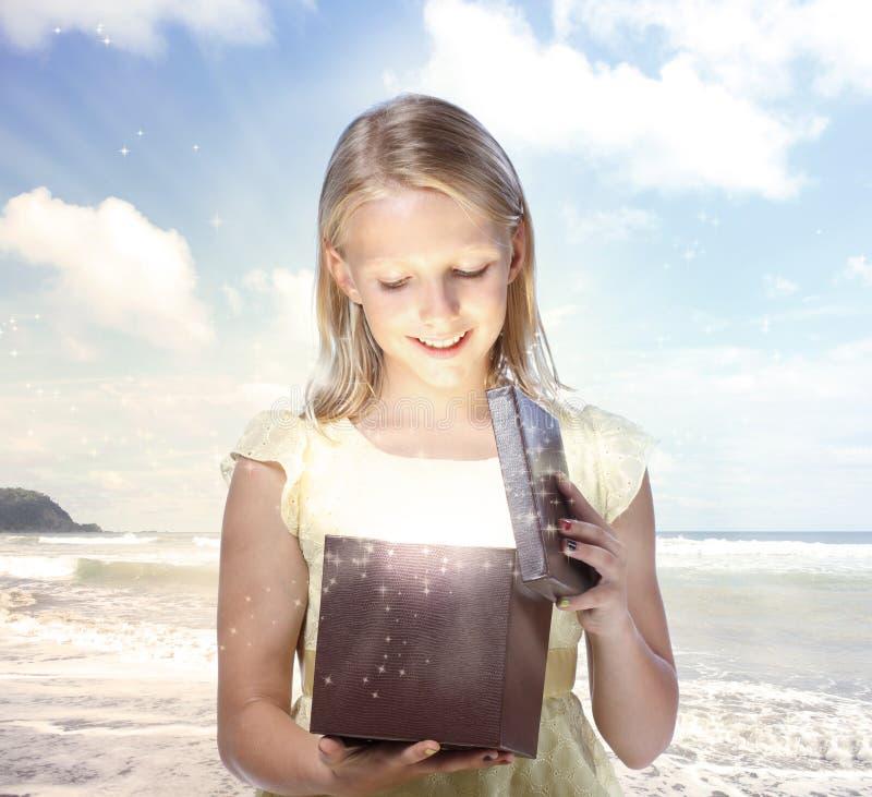 Junges blondes Mädchen, das einen Geschenk-Kasten öffnet stockfotos