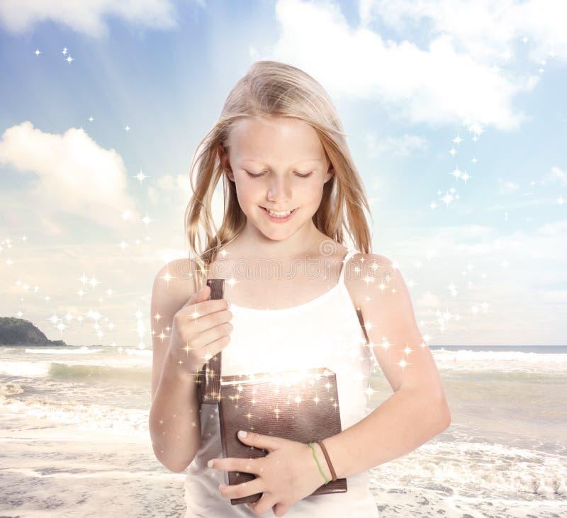 Junges blondes Mädchen, das einen Geschenk-Kasten öffnet stockfotografie