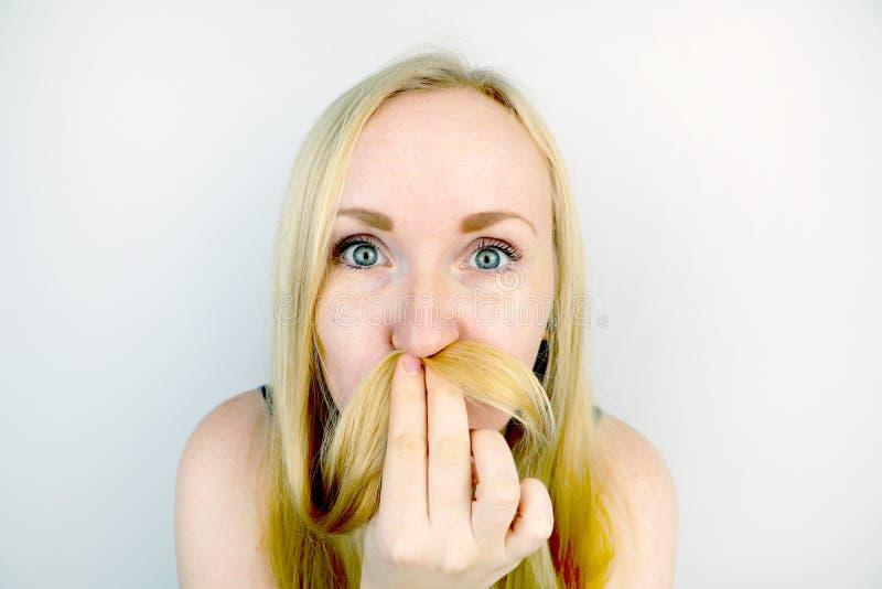 Junges blondes Mädchen, das herum, einen Schnurrbart aus Haar heraus herstellend täuscht Studioschießen, Gelächter stockfotografie