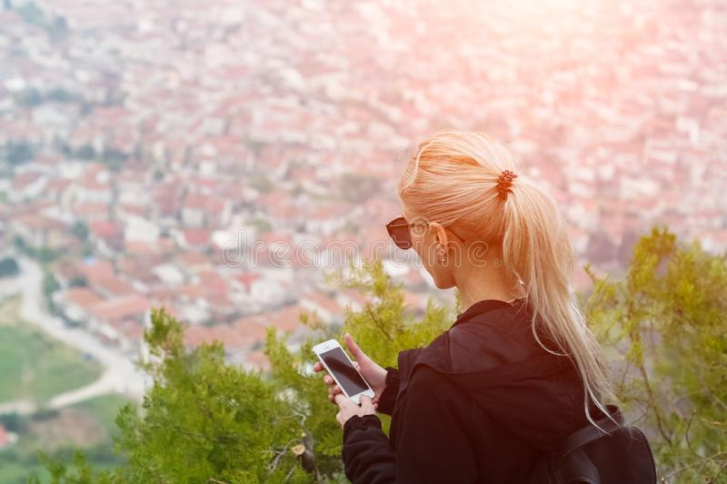 Junges blondes Mädchen, das Smartphone in den Bergen mit Sonnenlicht verwendet stockfotos