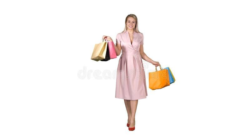 Junges blondes M?dchen in der rosa Kleidervertretung zu den Kameraeinkaufstaschen und im Gehen auf wei?en Hintergrund stockfotografie