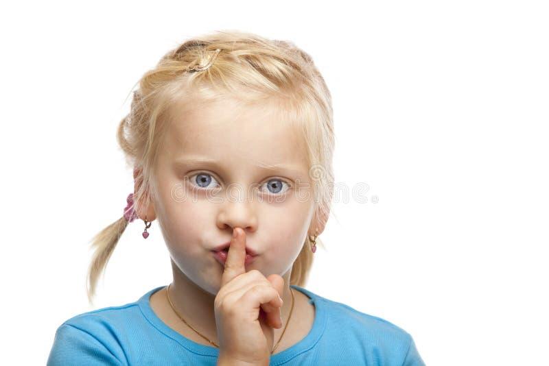 Junges blondes Mädchen hält Finger auf Mund an stockbilder