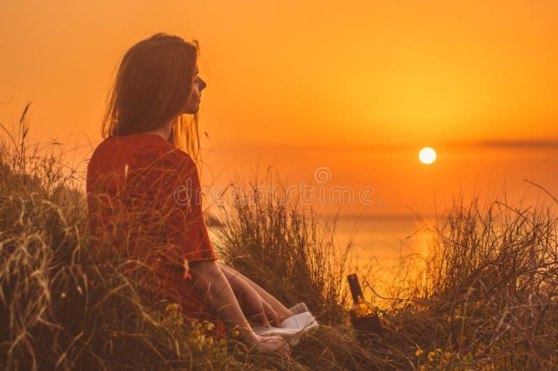 Junges blondes Mädchen im roten Kleid, das am Abend auf dem Strand sitzt stockbild