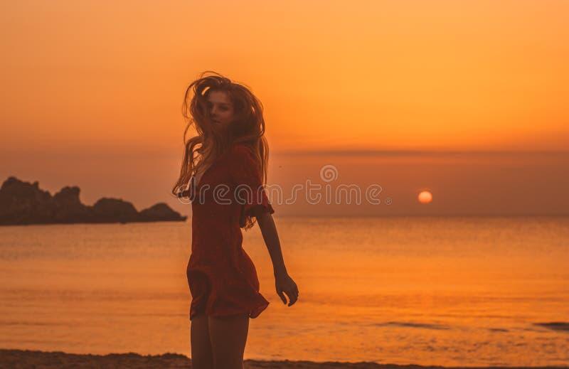 Junges blondes Mädchen im roten Kleidertanzen am Abend auf dem Strand stockfoto