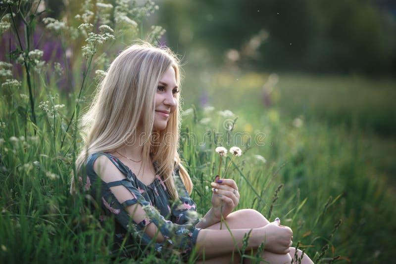 Junges blondes Mädchen mit dem langen Haar, das im Gras liegt stockbilder