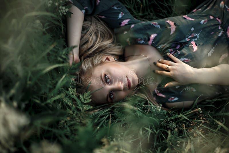 Junges blondes Mädchen mit dem langen Haar, das im Gras liegt stockfotos
