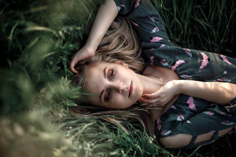 Junges blondes Mädchen mit dem langen Haar, das im Gras liegt lizenzfreie stockfotografie