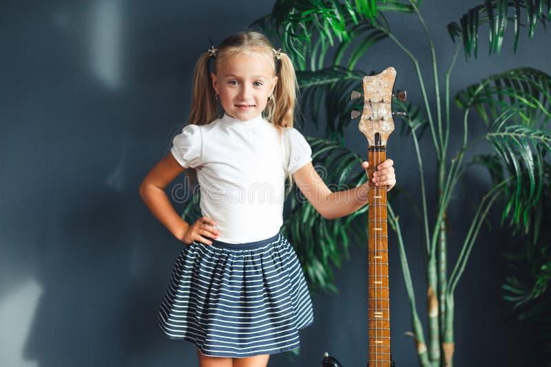 Junges blondes Mädchen mit Endstücken im weißen T-Shirt, im Rock und in den Sandalen mit der E-Gitarre zu Hause, die Kamera und L lizenzfreie stockfotos