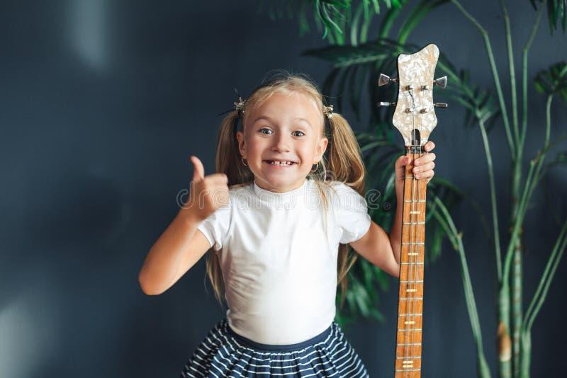 Junges blondes Mädchen mit Endstücken im weißen T-Shirt, im Rock und in den Sandalen mit E-Gitarre zeigt zu Hause den Daumen, der stockbild