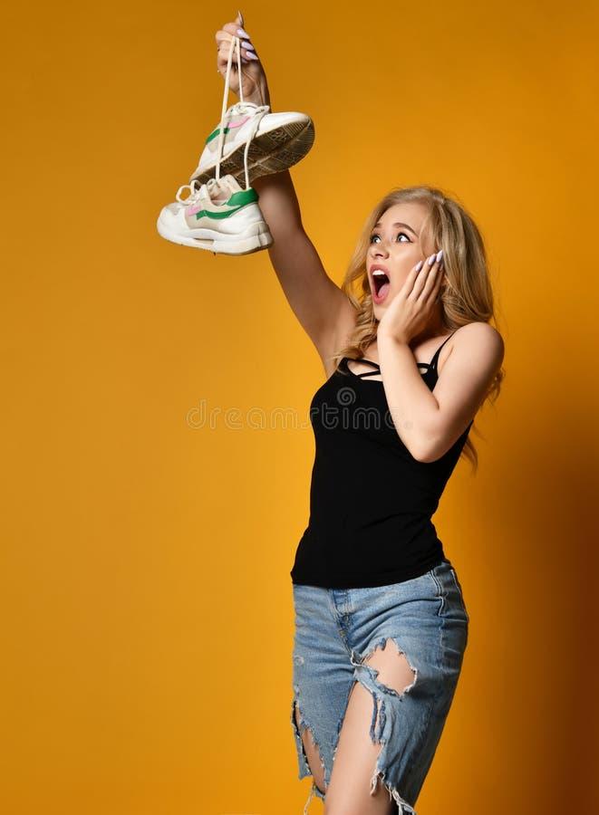 Junges blondes Mädchen wird durch alte Paare der schmutzigen Schuhe erschrocken Sie kann nicht glauben, dass es so schlecht ist lizenzfreie stockfotos
