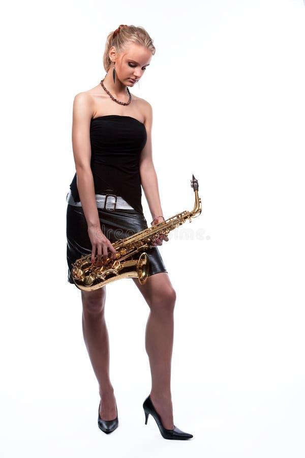 Junges blondes Musikermädchen mit Saxophon stockfotos