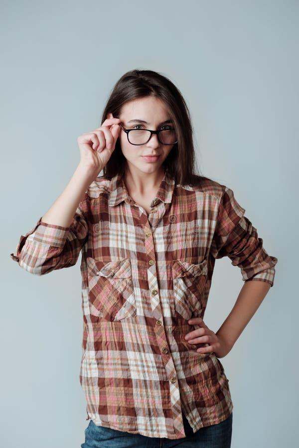 Junges brunette Mädchen im Karohemd, das Kamera iterested betrachtet lizenzfreies stockfoto