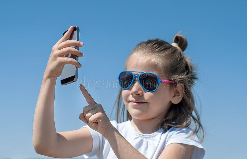 Junges brunette Mädchen am Sommertag die Sonne, selfie Porträt machend genießend Nettes Baby hält einen Handy in der Hand und Läc lizenzfreie stockfotos