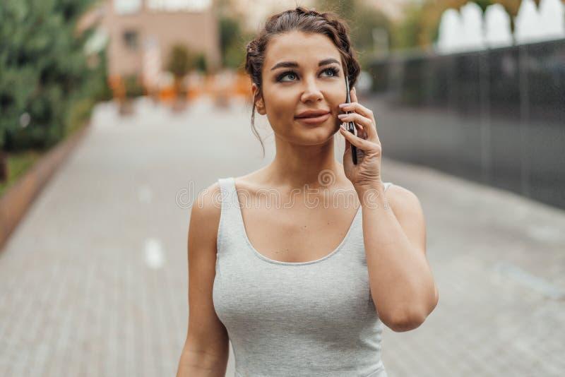 Junges Brunettemädchen, das durch Handy im Park zur Sommerzeit spricht stockfoto