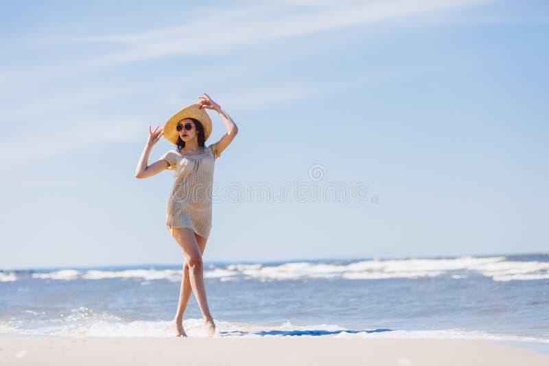 Junges Brunettemädchen, das liebenswürdig auf den Strand geht stockfotografie