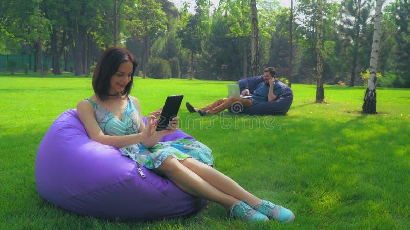 Junges Brunettemädchen sitzt in einem Stuhl in den Park- und Schlagseiten auf Ihrer Tablette lizenzfreie stockfotografie