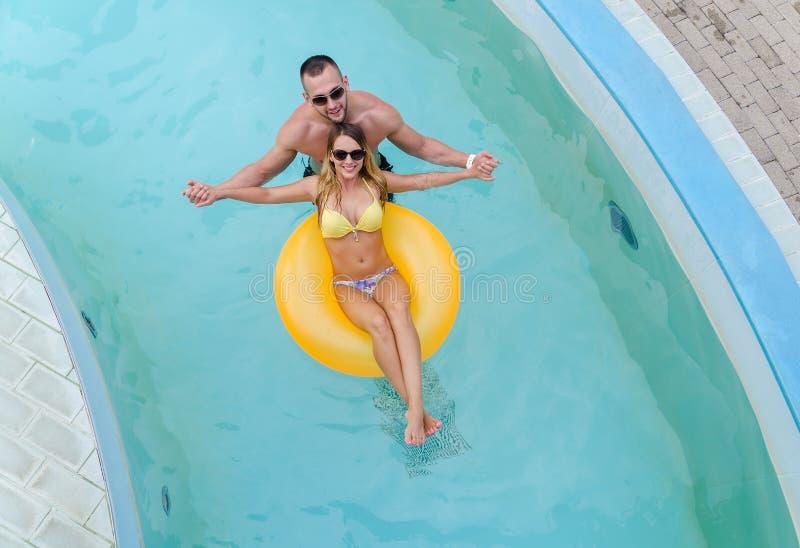 Junges cople, das Spaß im Wasser mit gelber Matratze hat stockfoto