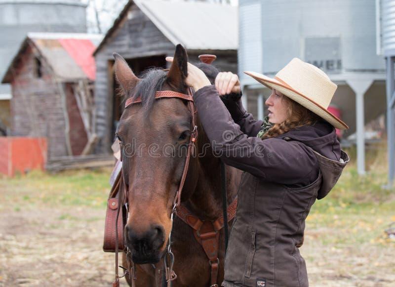 Junges Cowgirl, das zu einer Pferdefahrt fertig wird stockfotografie