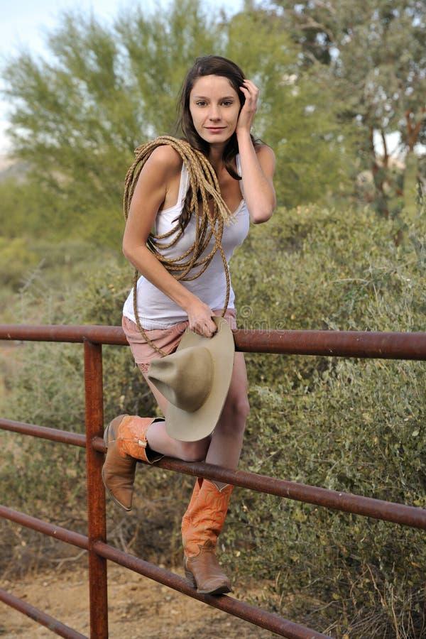 Junges Cowgirl-steigender Zaun stockfoto