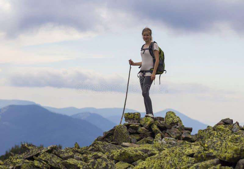 Junges dünnes blondes touristisches Mädchen mit dem Rucksack und Stock, die O stehen lizenzfreies stockbild