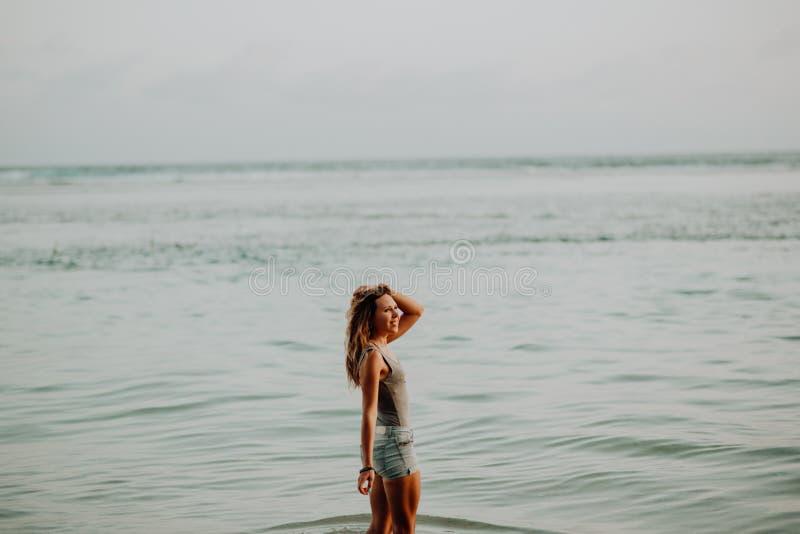 Junges dünnes Schönheitsmädchen auf Sonnenuntergangstrand, indie Art Eine Struktur der Steine, felsige Bruten lizenzfreie stockfotos