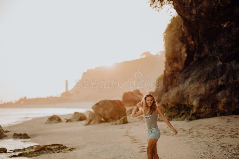 Junges dünnes Schönheitsmädchen auf Sonnenuntergangstrand, indie Art Eine Struktur der Steine, felsige Bruten lizenzfreie stockfotografie