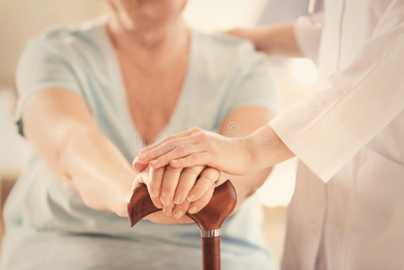 Junges Doktorhändchenhalten der älteren Frau lizenzfreie stockbilder