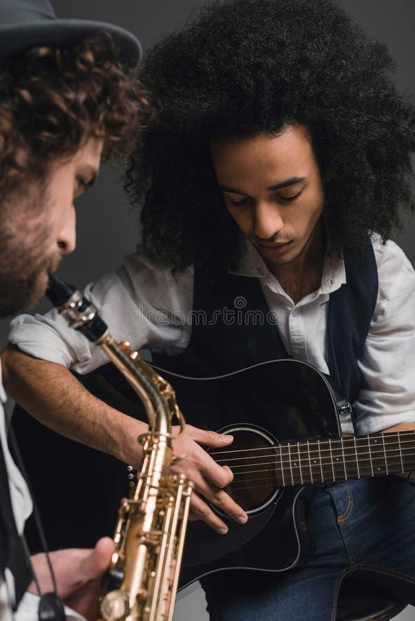 junges Duo von den Musikern, die Saxophon und Akustikgitarre spielen lizenzfreies stockbild