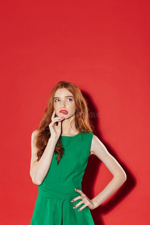 Junges durchdachtes Mädchen der Rothaarigen, das ihre Lippe beißt stockbild