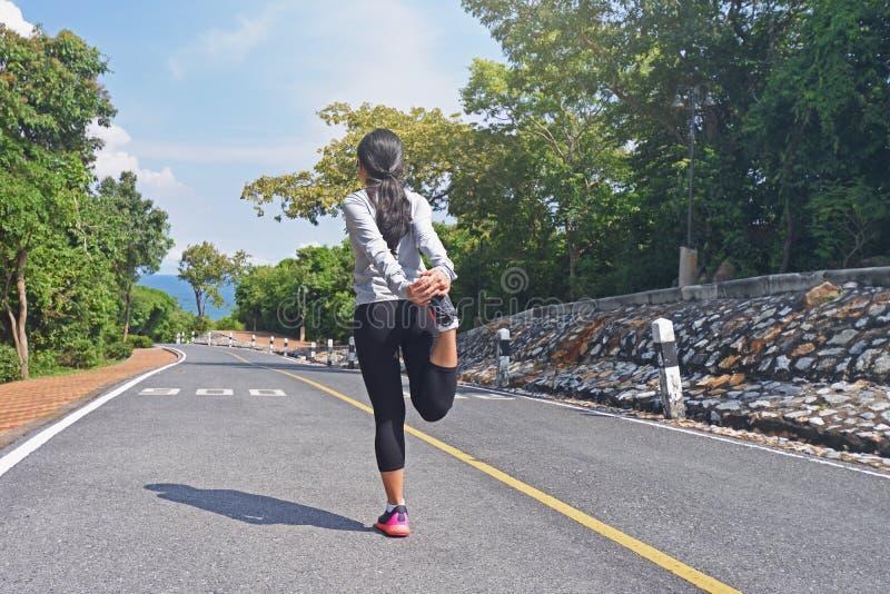 Junges Eignungsfrauen-Läuferaufwärmen auf Straße bevor dem Rütteln stockfoto