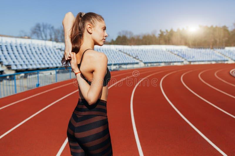 Junges Eignungsfrauen-Läuferaufwärmen bevor dem Laufen auf Bahn stockbild