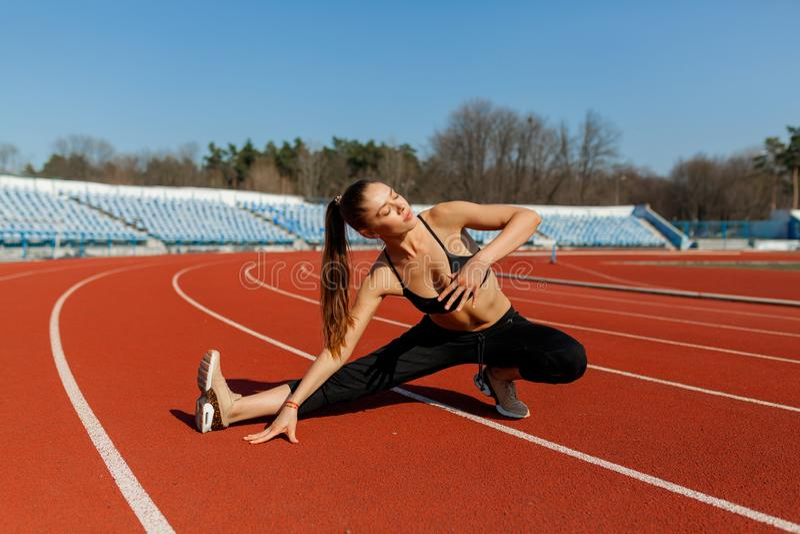 Junges Eignungsfrauen-Läuferaufwärmen bevor dem Laufen auf Bahn lizenzfreie stockfotografie