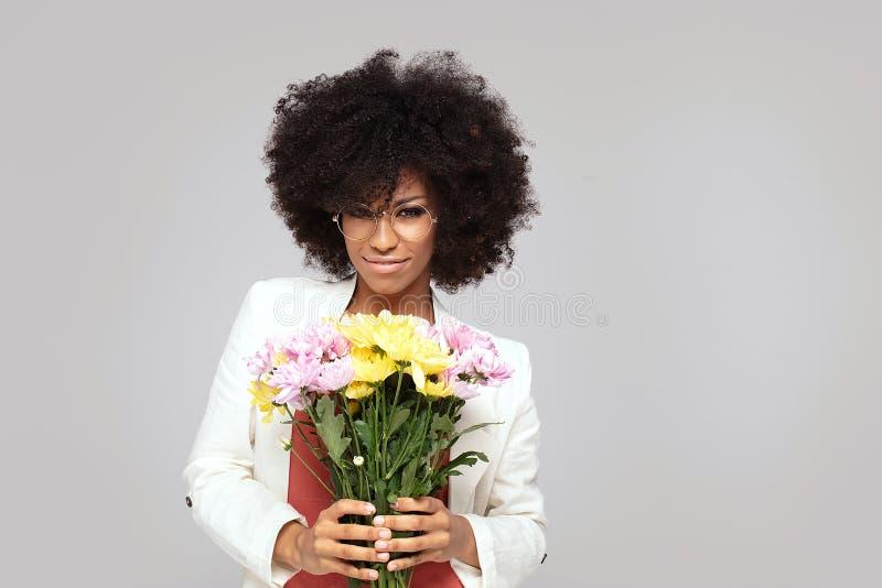 Junges elegantes Afromädchen mit Blumen lizenzfreie stockbilder