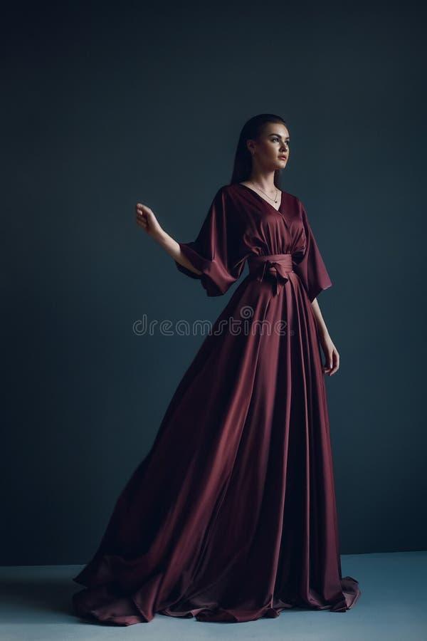 Junges elegantes Mädchen in Burgunder-Kleid lizenzfreie stockfotografie