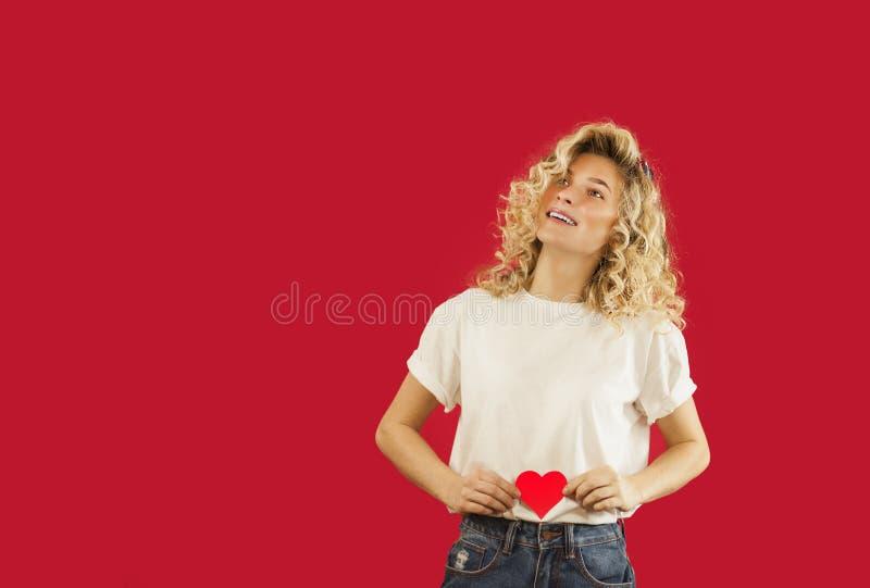 Junges emotionales Mädchen mit einem roten Herzen in ihren Händen steht auf einem lokalisierten roten Hintergrund Liebhabertagesk lizenzfreie stockfotografie