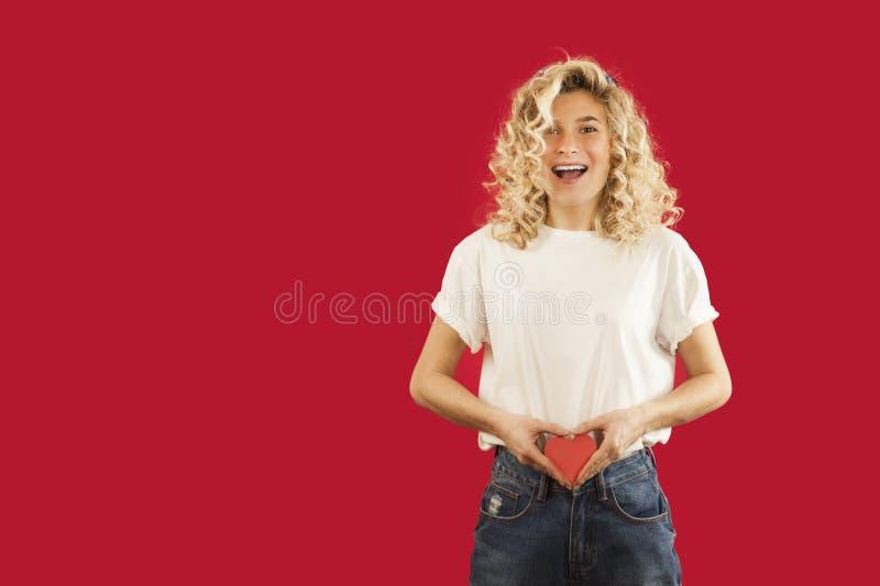 Junges emotionales Mädchen mit einem roten Herzen in ihren Händen steht auf einem lokalisierten roten Hintergrund Liebhabertagesk lizenzfreie stockbilder