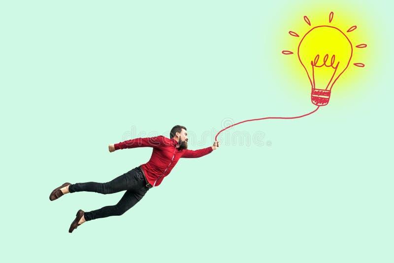 Junges erfolgreiches Geschäftsmannfliegen mit seiner perfekten Idee lustiger junger erfolgreicher bärtiger Mann im roten Hemd,  stockfotografie