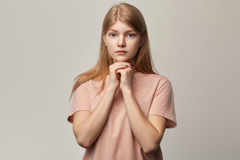 Junges ernstes trauriges unglückliches Mädchen, das über grauem Hintergrund plädiert stockfotografie