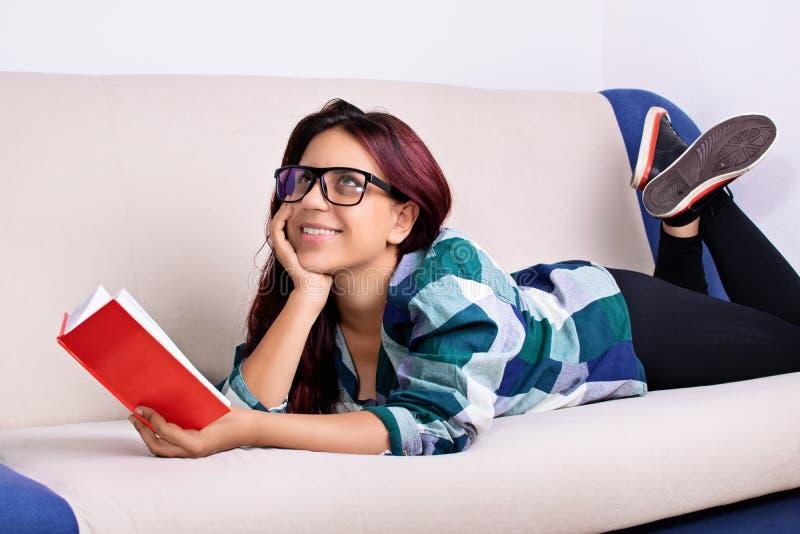 Junges fantasierendes Mädchen beim Ablesen eines Buches lizenzfreie stockbilder