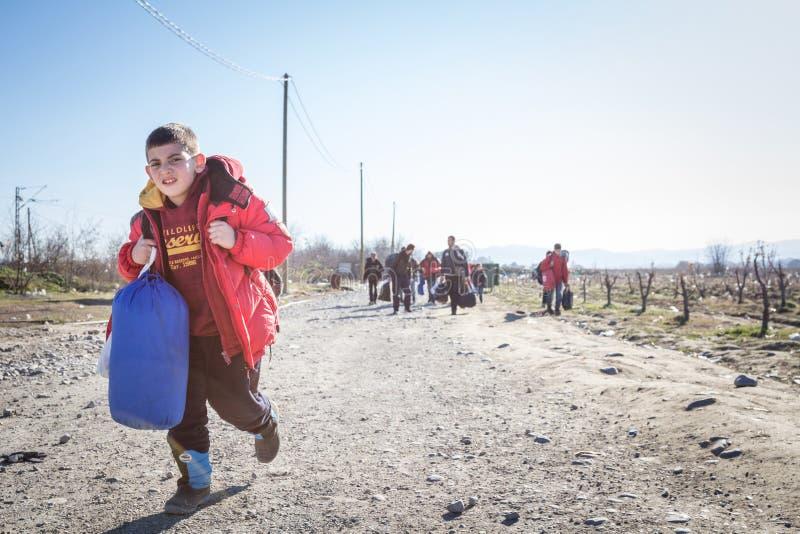 Junges Flüchtlingskind, das schweren Rucksack auf der Grenze Griechenlands Mazedonien, zwischen Städten von Eidomeni Idomeni u. G stockfotografie