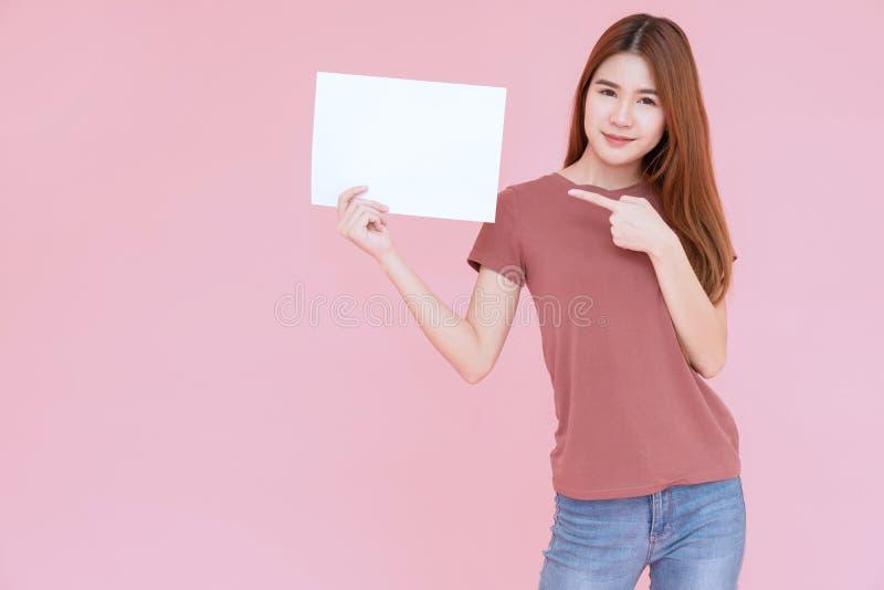 Junges Frauenholding-Werbeschildbrett Asiens l?chelndes und zeigenfinger Lokalisiertes Portr?t auf rosa Hintergrund mit Kopienrau lizenzfreies stockfoto