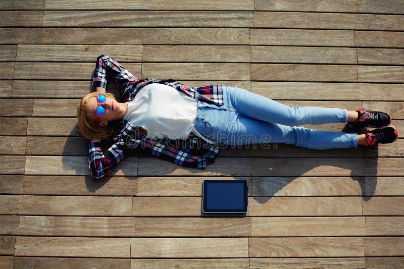 Junges Fraulügen entspannt auf einer Anlegestelle stockbild