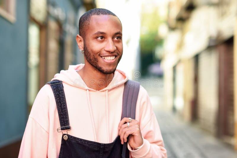 Junges gehendes Lächeln des schwarzen Mannes hinunter die Straße lizenzfreie stockfotografie